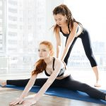 Charming focused young woman doing split and stretching with trainer