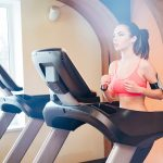 Pretty focused young woman athlete in earphones running on treadmill in gym